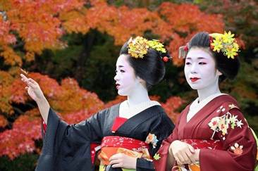 Maiko girls or young geisha admires scarlet maple leaves as they enjoy a sunny autumn day before they hold a tea party in Kyoto, western Japan 25 November 2006. Miko girls show off their Japanese traidtional dance performance and serve green teas to their customers. AFP PHOTO / Yoshikazu TSUNO (Photo credit should read YOSHIKAZU TSUNO/AFP/Getty Images)